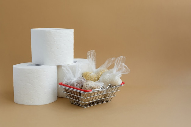 Toilet paper and various cereals in small plastic bags in grocery basket rice and oatmeal buckwheat and millet