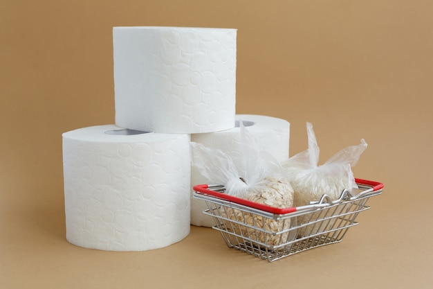 Toilet paper and various cereals in small plastic bags in grocery basket rice and oatmeal