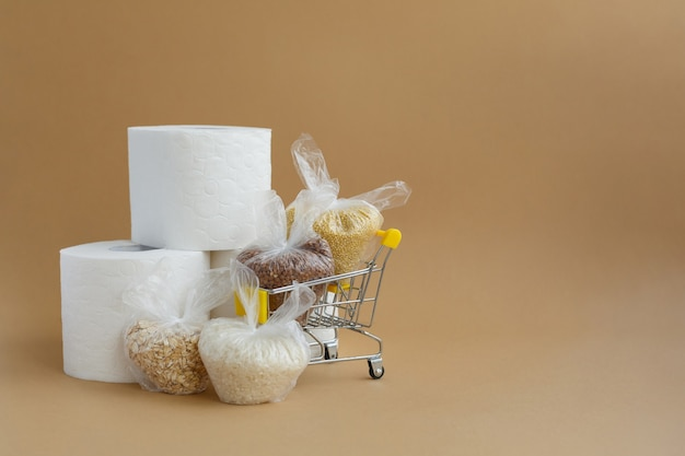 Toilet paper and various cereals in small plastic bags in grocery cart rice and oatmeal buckwheat and millet