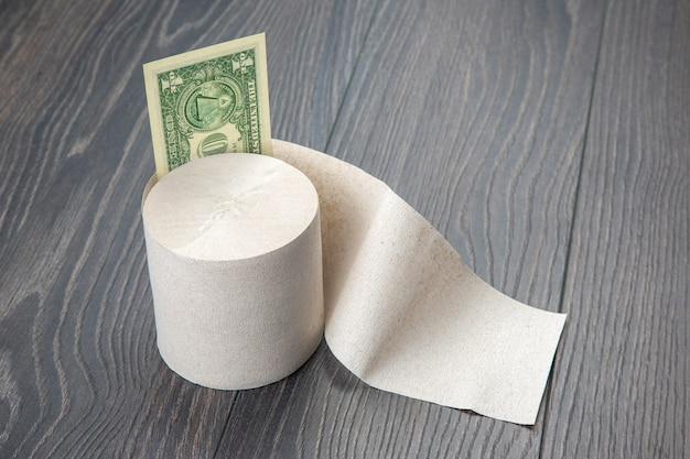 Туалетная бумага с долларовой банкнотой на деревянных фоне