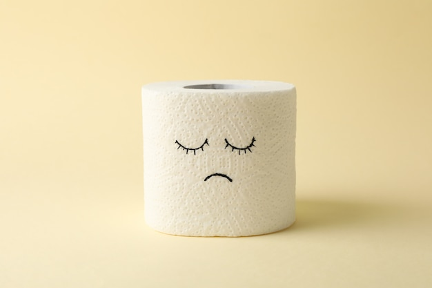 Toilet paper with sad face on beige