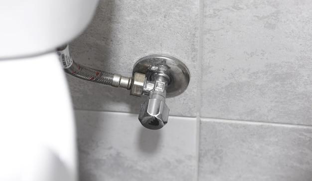 トイレパイプのクローズアップ、バスルームの配管コンセプトの背景