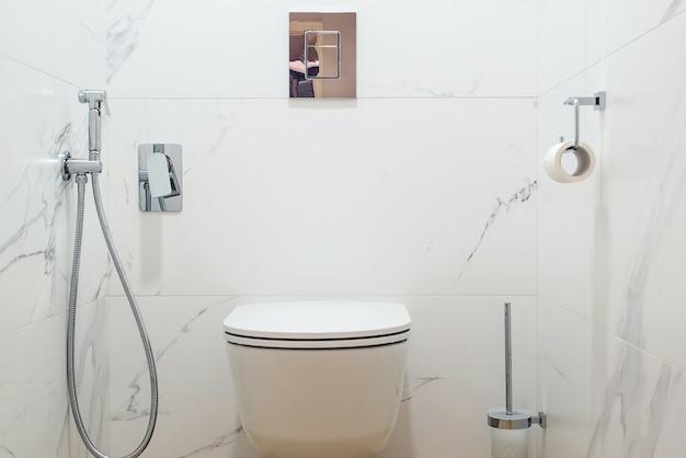 Туалетная комната с современной сантехникой. унитаз в интерьере современной ванной комнаты. современный интерьер туалета, вид спереди.