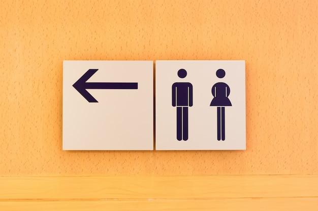 木製の背景にトイレの看板と方向
