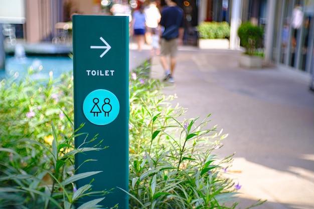 정원이있는 파스텔 그린 보드에 화장실 로그인하십시오. 화장실 화장실 방에 성별 남성과 여성의 상징. 화장실 아이콘을 설정합니다.