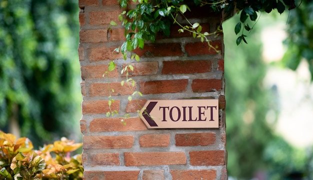 葉と赤レンガの壁にトイレのサイン