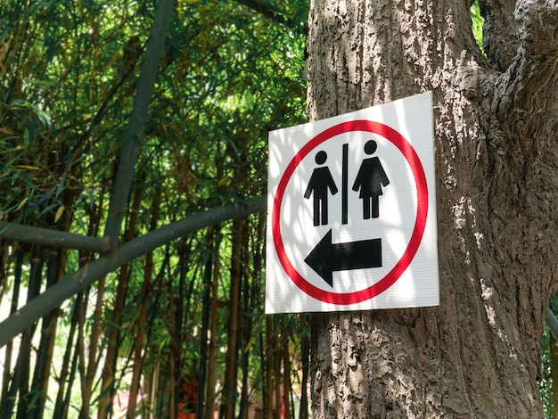Toilet sign with arrow inside red circle hanging on the tree