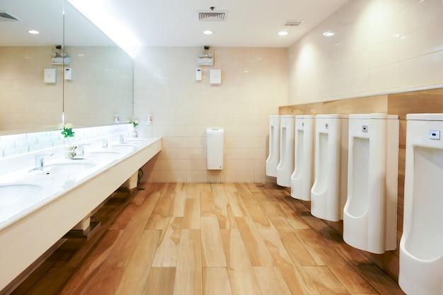 Интерьер унитаза в общественном туалете с мытьем рук и зеркалом, чистый туалет