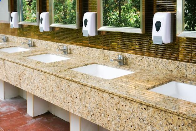 Интерьер унитаза общественного туалета с мытьем рук и зеркалом золотой, чистый туалет