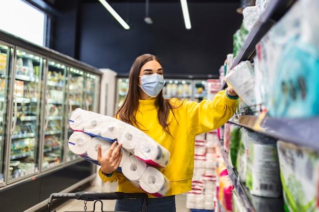 화장지 부족 : 바이러스 전염병 발생시 패닉 구매 및 제품 비축으로 인해 화장지 용품을 쇼핑하는 위생 마스크를 가진 여성.