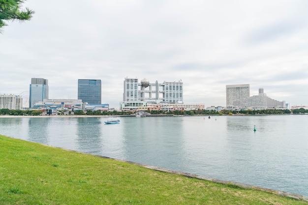 Tokyo cruise boat cruising infront of odaiba aqua city shopping mall and fuji television building, odaiba.