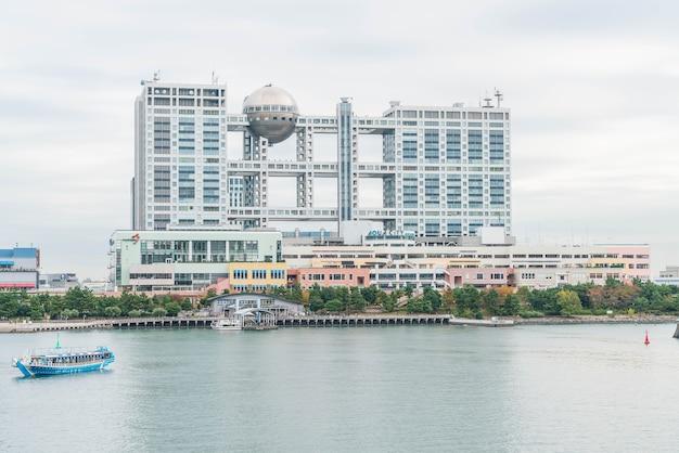 오다이바 아쿠아 시티 쇼핑몰과 오다이바 후지 텔레비전 빌딩에서 크루즈하는 도쿄 크루즈 보트.