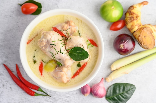 Tom kha kai in a bowl with kaffir lime leaves, lemongrass, red onion, galangal and chilli.