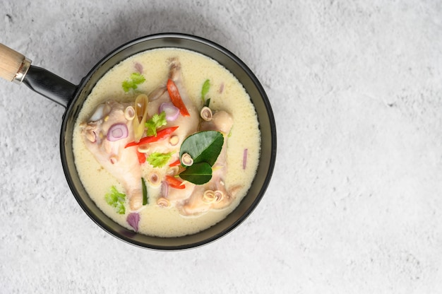 Tom kha kai in a pan frying with kaffir lime leaves, lemongrass, red onion, galangal and chilli.