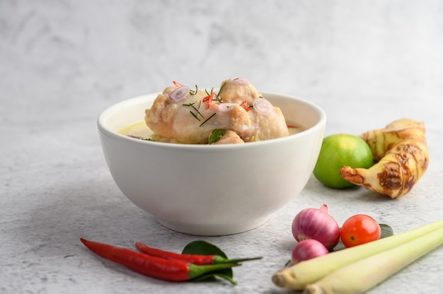 Tom kha kai в миске с листьями кафрского лайма, лемонграссом, красным луком, галангалом и перцем чили.