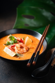 Tom yam kung spicy thai soup with shrimp in a black bowl on a dark surface, selective focus
