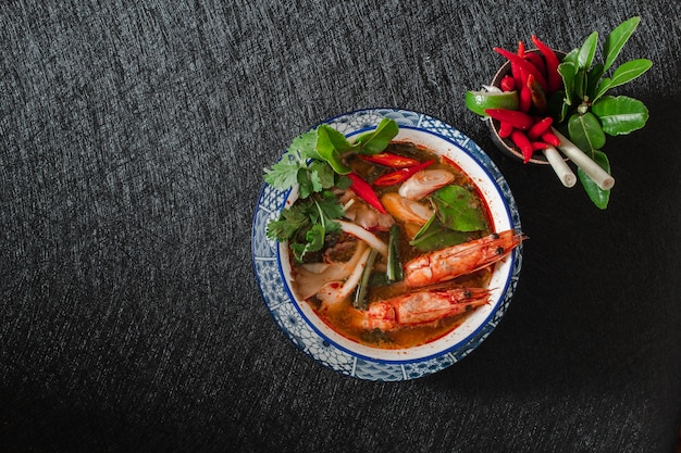 Tom yam kung spicy thai soup with shrimp on dark.