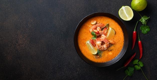 Том ям кунг острый тайский суп с креветками в черной миске на темном каменном фоне, вид сверху, копия пространства