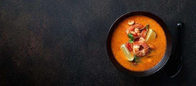 어두운 돌 배경, 평면도, 복사 공간에 검은 그릇에 새우와 톰 얌 쿵 매운 태국 수프