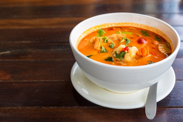 Tom yam kung spicy thai soup with shrimp in white bowl on wood table..