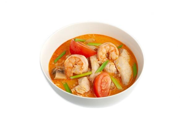 하얀 접시에 담긴 톰 얌 수프. 해산물과 닭고기. 파로 장식되어 있습니다. 클로즈업, 상위 뷰입니다. 흰색 배경.