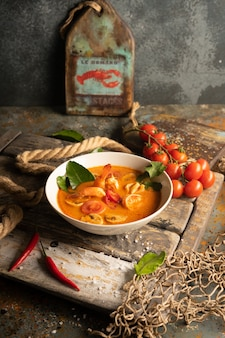 Tom yam soup with shrimp, squid and hot pepper on textured wooden board