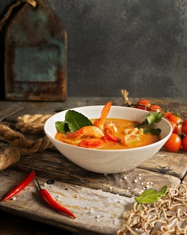Tom yam soup with shrimp, squid and hot pepper on textured wooden board.