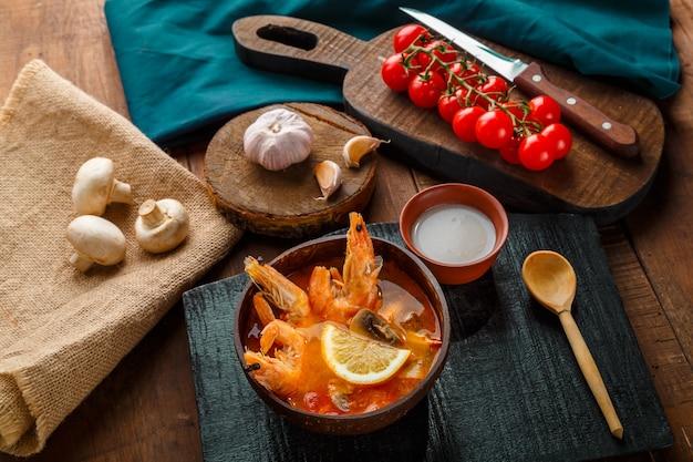 Суп том ям с креветками и кокосовым молоком на столе на черной доске и ложке. горизонтальное фото