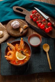 Суп том ям с креветками и кокосовым молоком на столе на черной доске и ложке. вертикальное фото