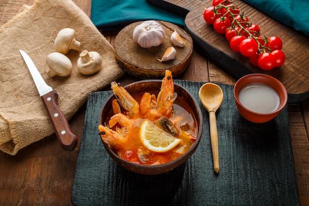 Суп том ям с креветками и кокосовым молоком на столе на черной доске рядом с ингредиентами и ложкой. горизонтальное фото