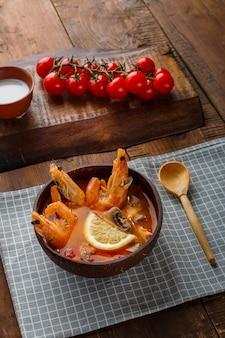 Суп том ям с креветками и кокосовым молоком на столе на клетчатой салфетке рядом с овощами и деревянной ложкой. вертикальное фото