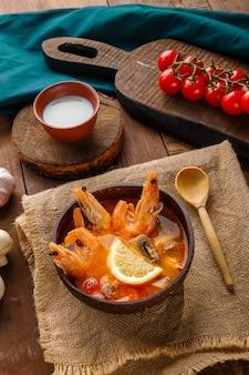 Суп том ям с креветками и кокосовым молоком на столе на льняной салфетке рядом с овощами