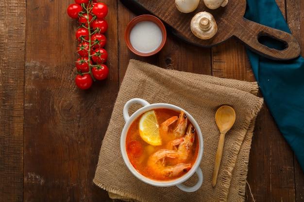 Суп том-ям с креветками и кокосовым молоком на столе на салфетке рядом с кокосовыми грибами и помидорами. горизонтальное фото