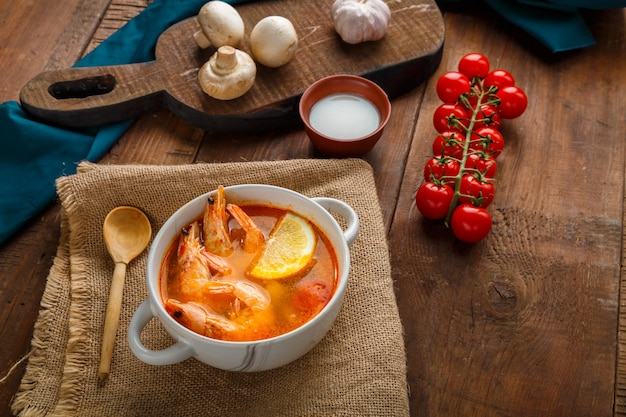 Суп том ям с креветками и кокосовым молоком на столе на салфетке рядом с кокосовыми грибами и помидорами