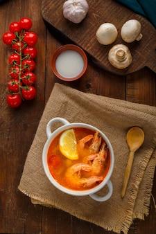 Суп том ям с креветками и кокосовым молоком на столе на деревянных досках возле молочных грибов