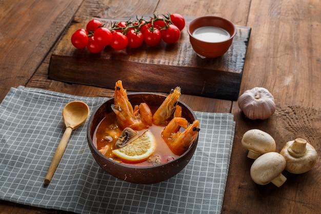 Суп том ям с креветками и кокосовым молоком на столе на клетчатой салфетке рядом с овощами