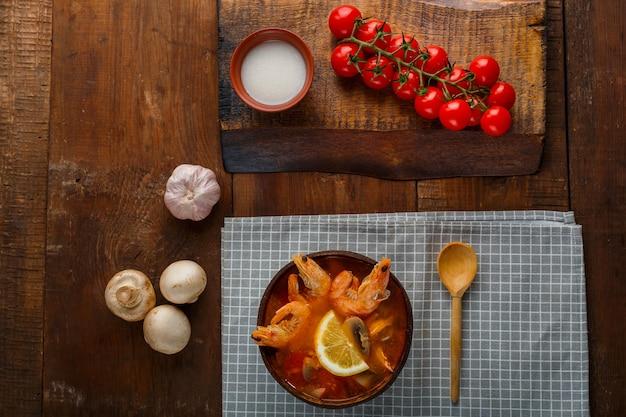 Суп том ям с креветками и кокосовым молоком на столе на клетчатой салфетке