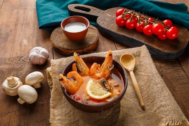 Суп том ям с креветками и кокосовым молоком на столе на льняной салфетке рядом с овощами и ложкой. горизонтальное фото
