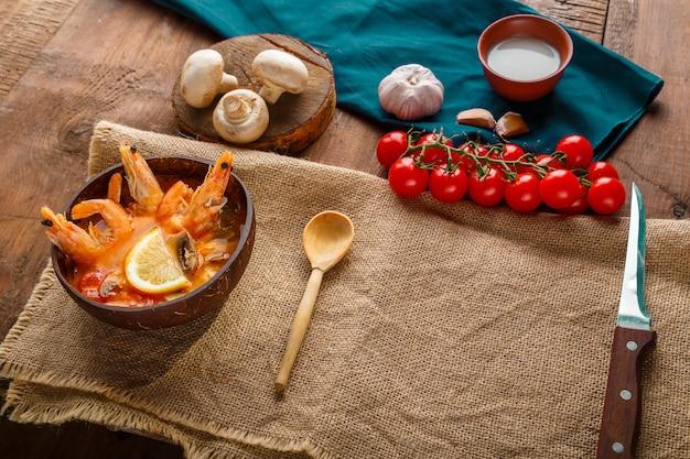 Суп том ям с креветками и кокосовым молоком на столе на салфетке рядом с ингредиентами. копировать пространство. горизонтальное фото