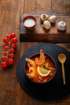Суп том-ям с креветками и кокосовым молоком на столе на круглой доске рядом с молочными грибами и помидорами. вертикальное фото