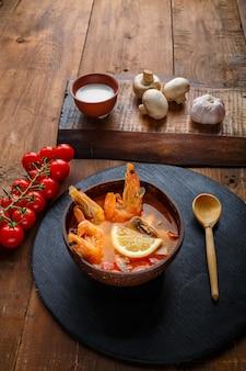 Суп том-ям с креветками и кокосовым молоком на столе на круглой доске рядом с молочными грибами и помидорами.