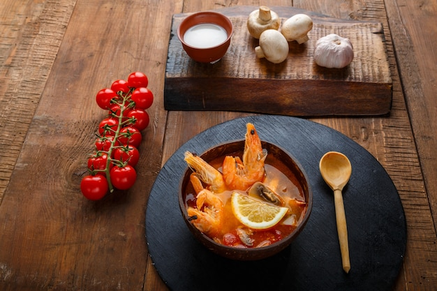 Суп том ям с креветками и кокосовым молоком на столе на круглой доске возле молока