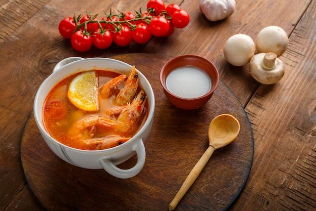 Суп том ям с креветками и кокосовым молоком на столе на круглой доске рядом с кокосовым молоком и ложкой.