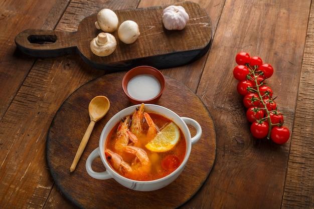 Суп том-ям с креветками и кокосовым молоком на столе на круглой доске рядом с кокосовыми грибами и помидорами.