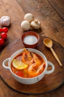 Суп том ям с креветками и кокосовым молоком на столе на круглой доске рядом вертикальное фото с кокосовым молоком и помидорами.