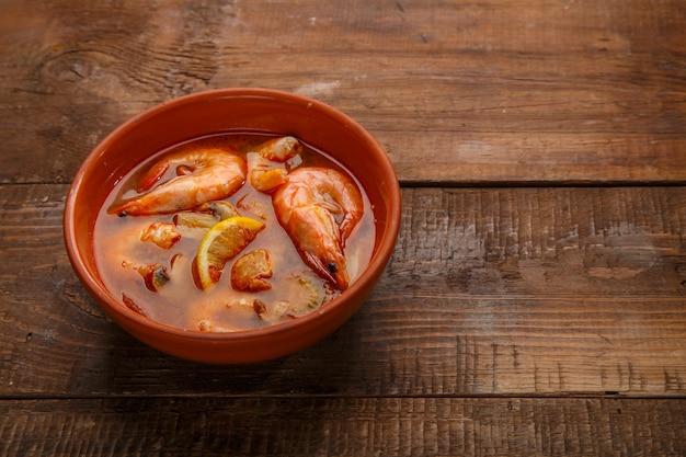 木製のテーブルの上の皿にエビが入ったトムヤムクンのスープ。横の写真
