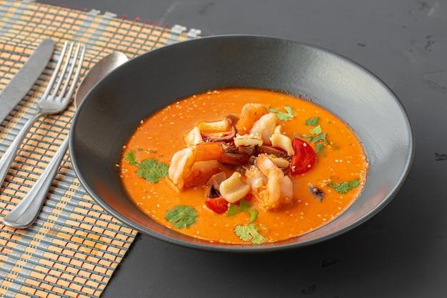 灰色のテーブルの上の黒いボウルにトムヤムタイのスープ