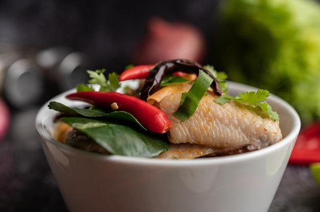トムヤムチキンと唐辛子、コリアンダー、乾燥唐辛子、コブミカンの葉、マッシュルーム、レモングラスをボウルに入れて