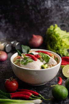 Tom yum chicken with chili, coriander, dried chili, kaffir lime leaves, mushroom and lemongrass in a bowl