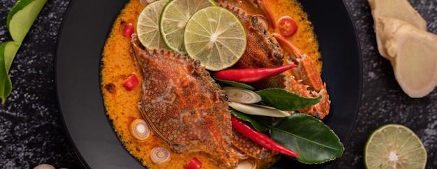 접시에 레몬, 칠리, 토마토, 마늘, 레몬 그라스, 카피 르 라임 잎을 넣은 톰얌 크랩